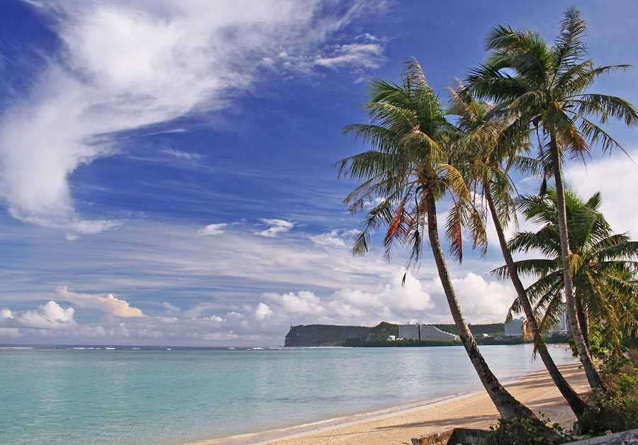 Guam Beach early morning in Tumon Bay Guam with two palm trees and Two Lover's Point in the background